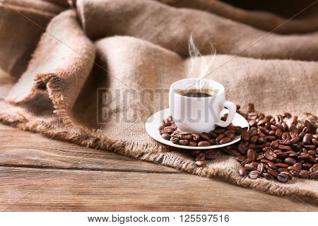 Cup of coffee with sackcloth on table close-up