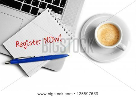 Register now written in notebook, laptop and cup of coffee on white background, top view