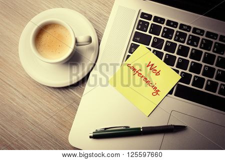 Web conferencing written on sticky note, laptop? pen and cup of coffee on table, top view
