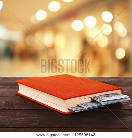Red book with nested dollar banknotes on bright background