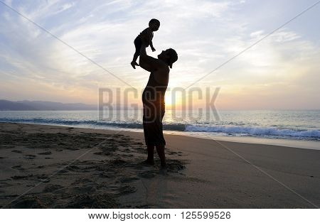 Father son is a silhouette of a father joyfully playing with his son at the beach at sunset.