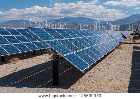 Solar Panels And Wind Turbines In Sunny Desert