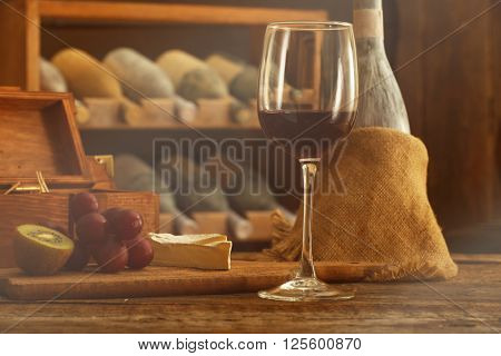 Aged bottles with glass of wine on wooden table