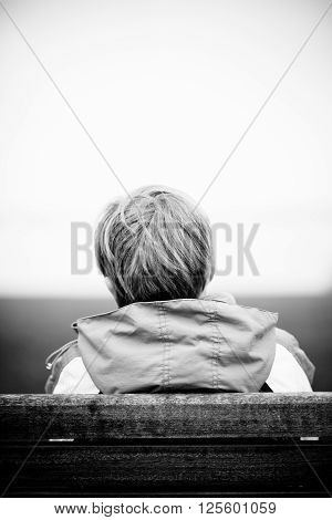 Rear View Of Boy In Coat On Bench Facing Lake
