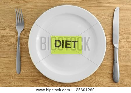 White plate with word diet on wooden background
