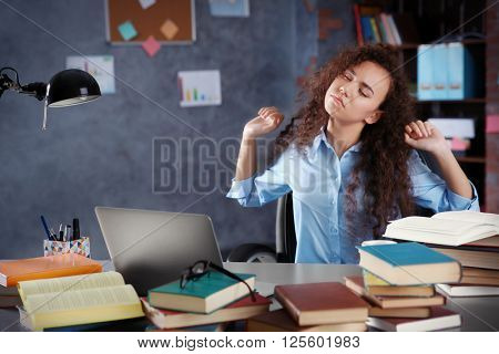 Tired girl with pile of books in office