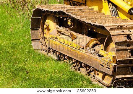 Muddy treads on bulldozer parked on green grass.