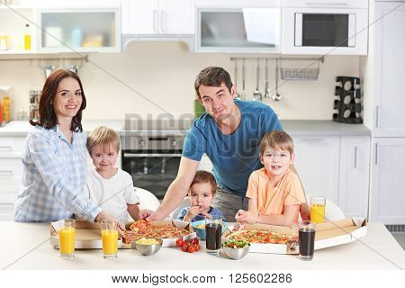 Happy family eating pizza in the kitchen together