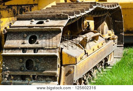 Detail of muddy tracks and treads on bulldozer parked on green grass.