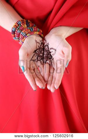 Female hands with henna tattoo on red fabric background