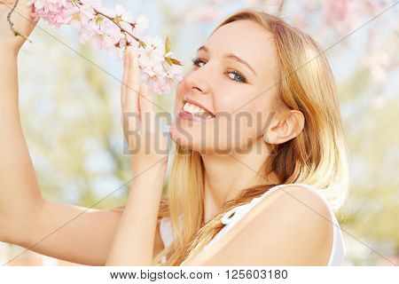 Happy blonde girl smelling scent of cherry blossoms in spring
