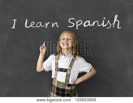 young sweet junior schoolgirl with blonde hair standing happy and smiling isolated in front of classroom blackboard holding chalk in children learning spanish language and education concept