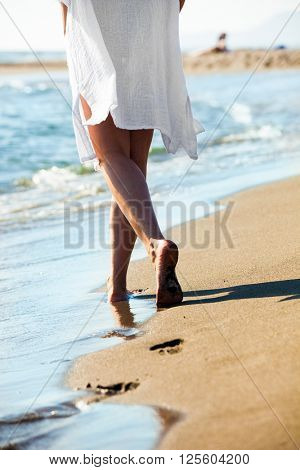 woman walk on sandy beach by the sea, lower body