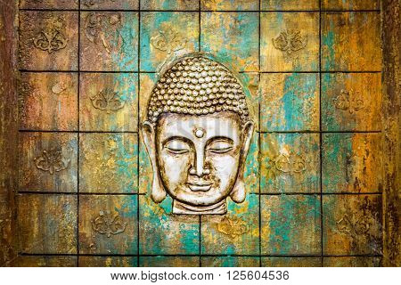 Head of Buddha carved in an old wooden door.