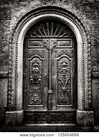 Old wooden gate with stone vault engraved with demonic figures.