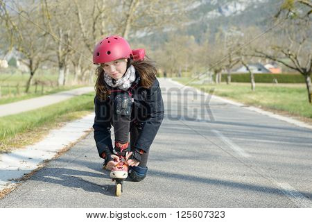 a pretty preteen girl on roller skates in helmet at a track