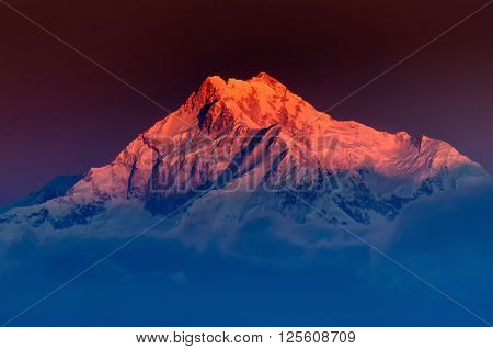 Beautiful first light from sunrise on Mount Kanchenjugha Himalayan mountain range Sikkim India. Blue coloured clouds surrounded the mountains at dawn