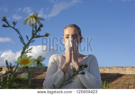 Young woman sneezing in a daisy flowers meadow. She is allergic to flowers