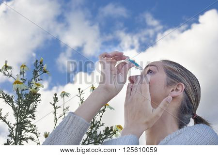 Young woman using eyedropper to treat irritated eyes at flowers meadow