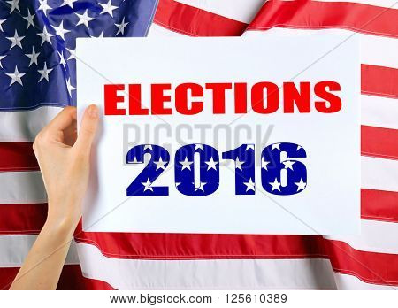 Hand holding card with text Elections 2016 on USA National Flag background
