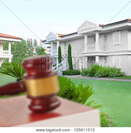 Gavel and books on wooden table on building background. Auction concept
