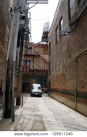 JOLIET, ILLINOIS / UNITED STATES - APRIL 12, 2015: A narrow alleyway between tall buildings in downtown Joliet.