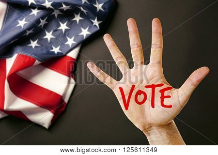 Male hand with text Vote and USA National Flag on black background
