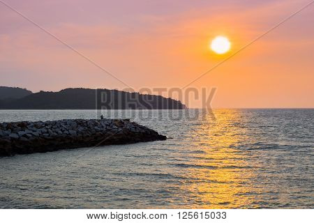 Person sitting on rocks watching sunset on Langkawi island in Malaysia with an orange sky