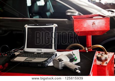 Diagnostic machine tools ready to be used with car in background.