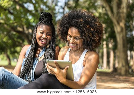 women using tablet computer in the park