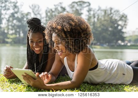 Latina girls using tablet computer in the park