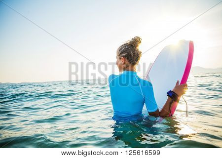 Young surfer girl is lerning to ride a wave.