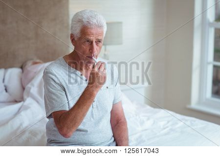 Senior man using thermometer while sitting on bed