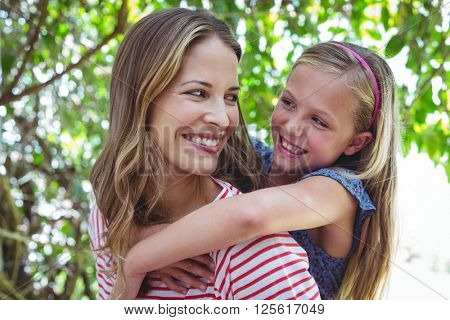 Happy mother giving piggy-back to daughter while standing outdoors