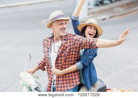 Excited couple waving hands on moped while riding in city