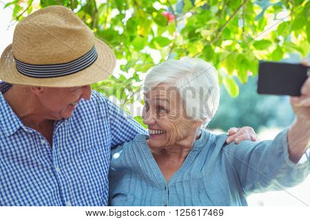 Cheerful retired couple taking self portrait while standing outdoors