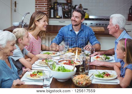 Happy multi generation family with grandparents sitting at dining table