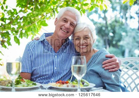 Portrait of happy retired couple with arm around while sitting at table