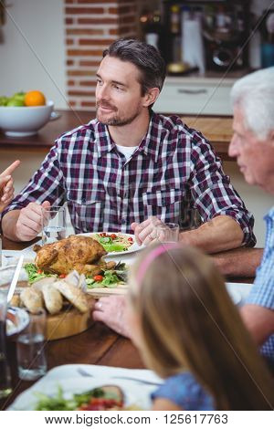Multi generation family sitting at dining table in home
