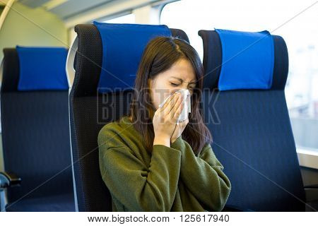 Woman sneezing inside train compartment