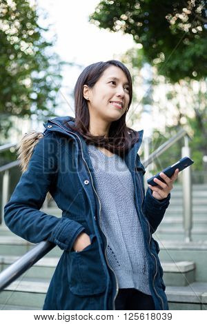 Woman use of mobile phone and looking far away