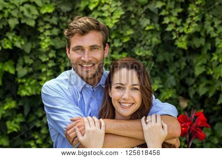 Portrait of happy couple hugging at front yard