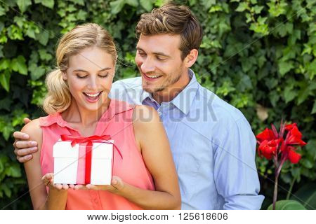 Romantic man giving gift to surprised woman at front yard