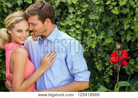 Romantic couple hugging in front yard
