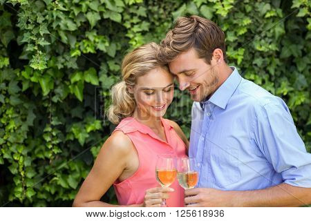 Romantic happy couple toasting wineglasses at front yard