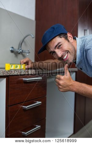 Portrait of smiling man showing thumbs up while using spirit level in kitchen
