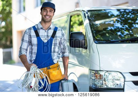 Portrait of happy carpenter with toolbox while standing by van