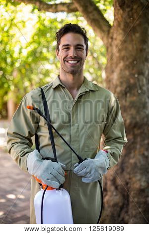 Portrait of happy worker with insecticide sprayer while standing by tree