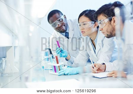Group of chemists looking at tubing