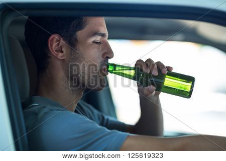 Close-up of man drinking alcohol while sitting in car
